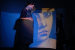 Dance performance with projected images on sheets.